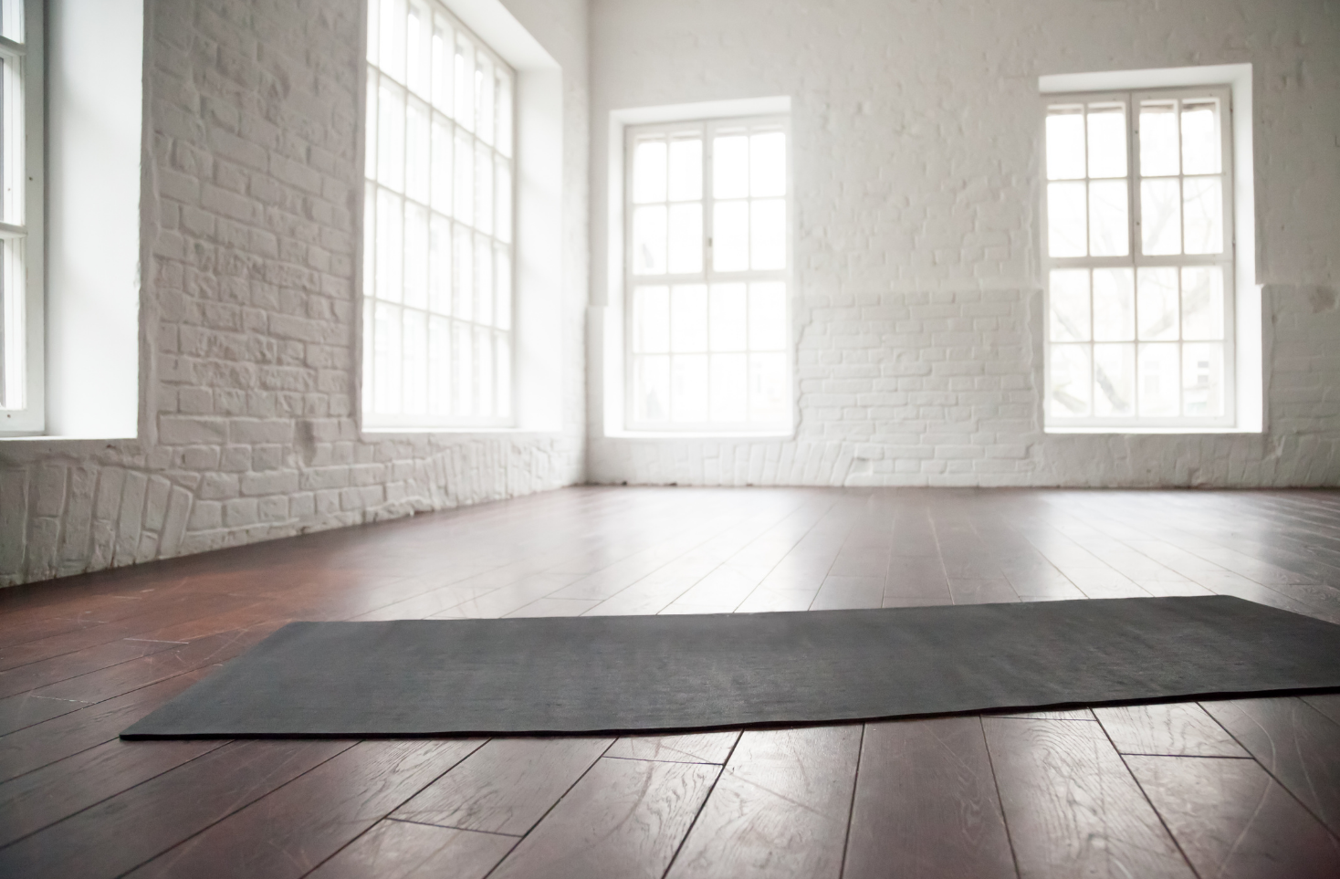 Empty yoga studio with a grey yoga mat inside.