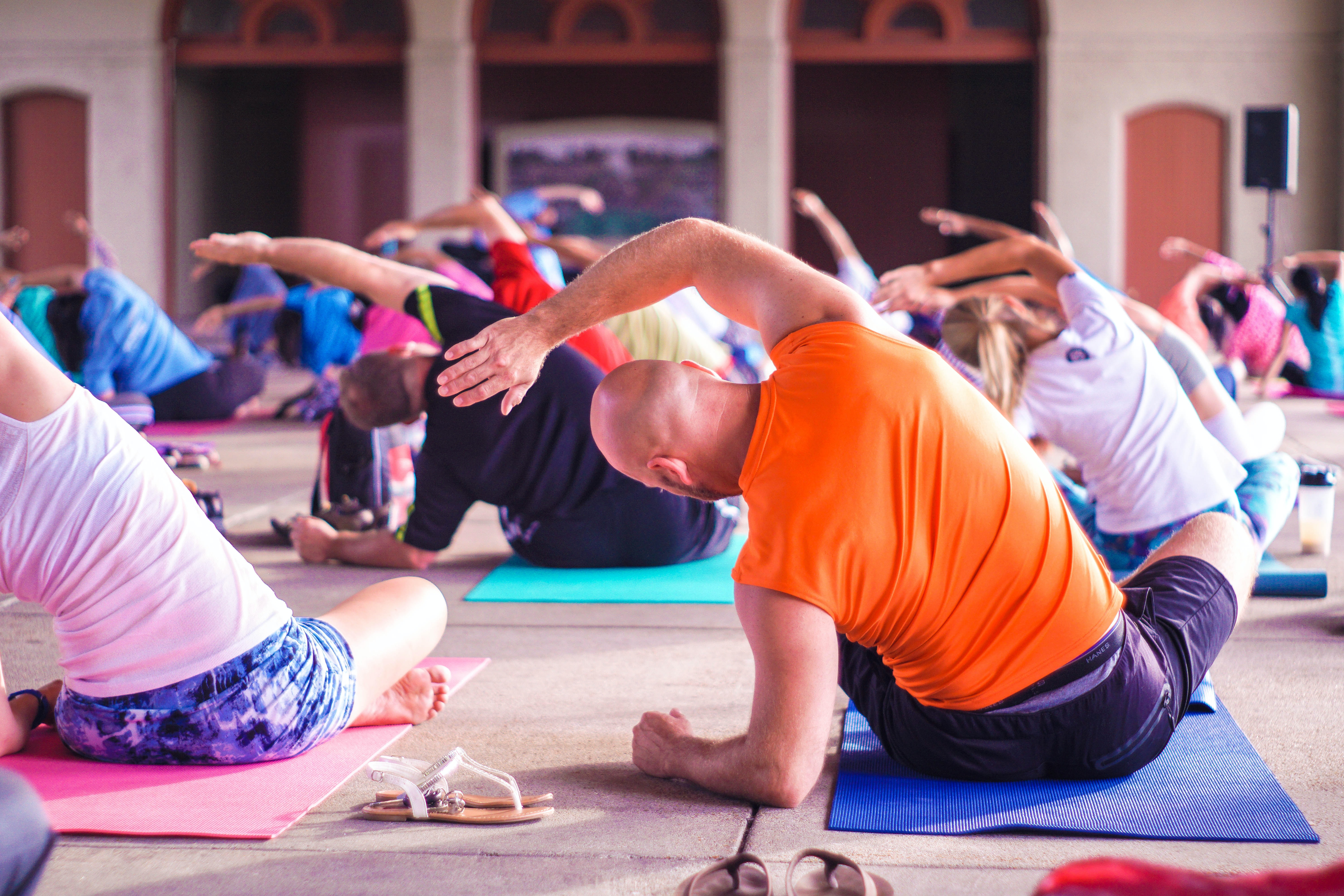A group of yogis bending left while attending a yoga class.