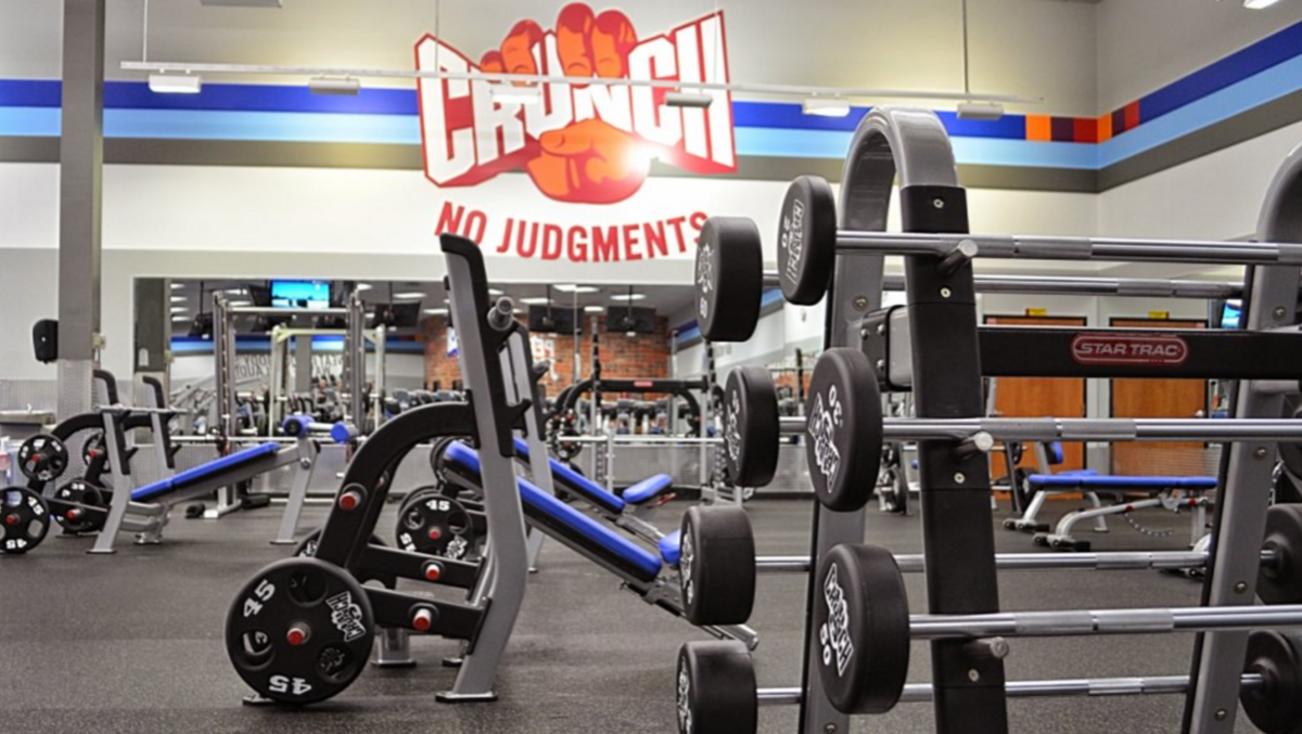"""Crunch fitness gym with different equipments and """"No Judgements"""" written on its wall."""