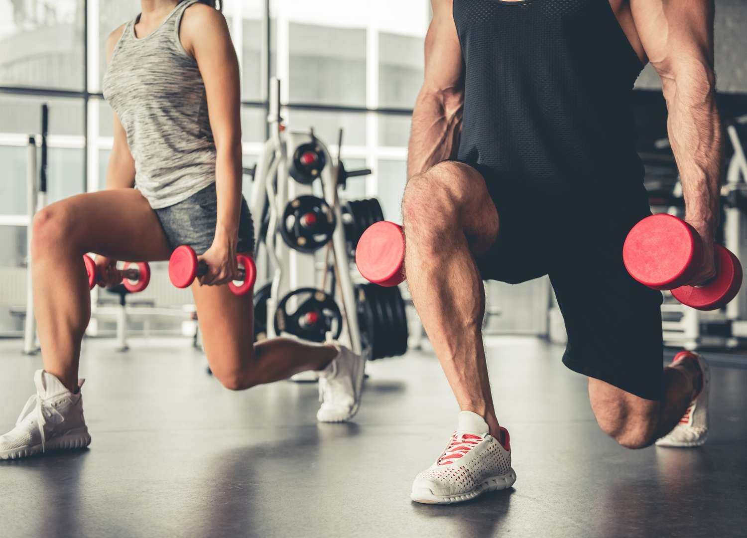 Two persons lifting dumbbells