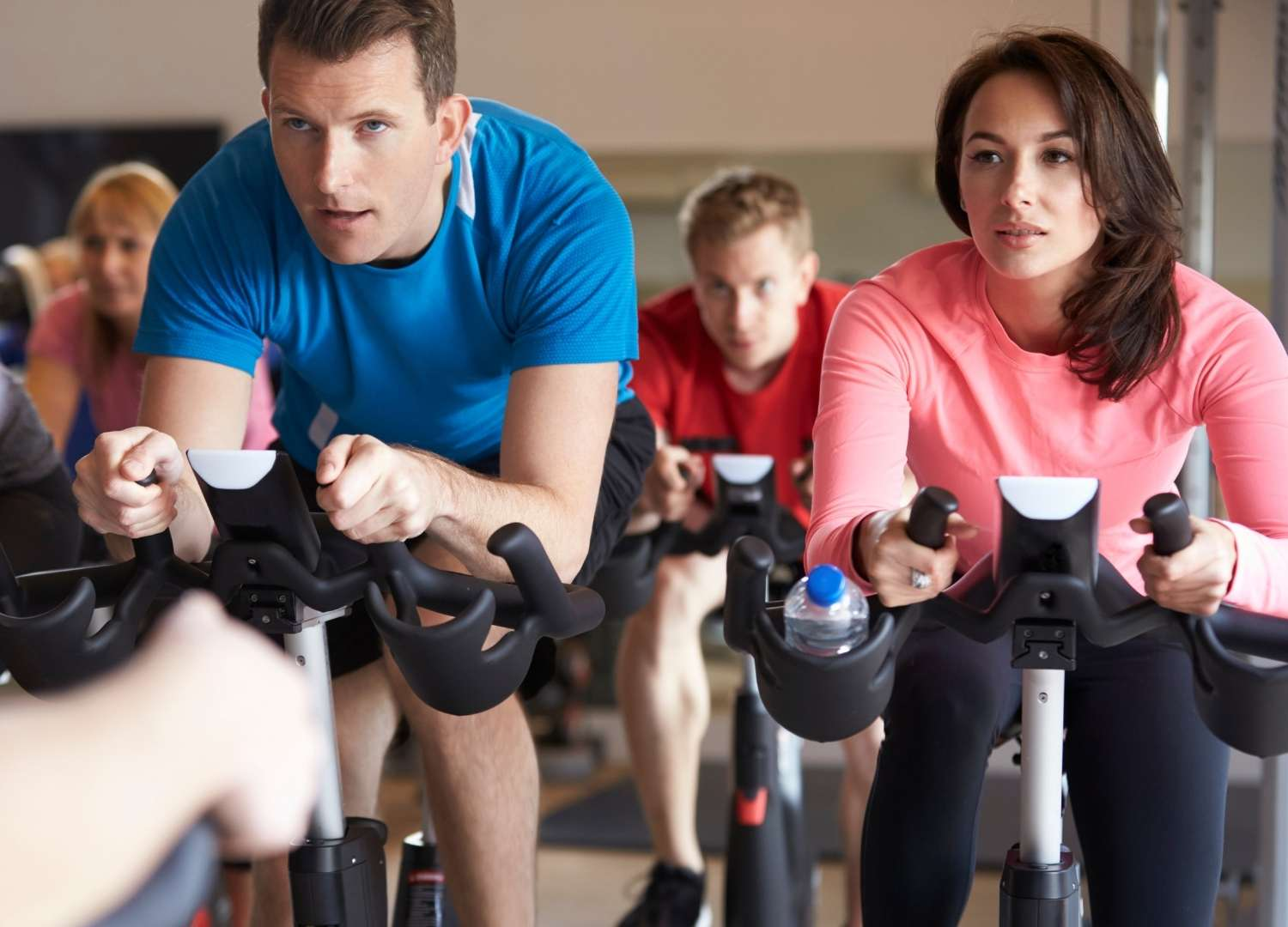 Group of people using gym-bikes