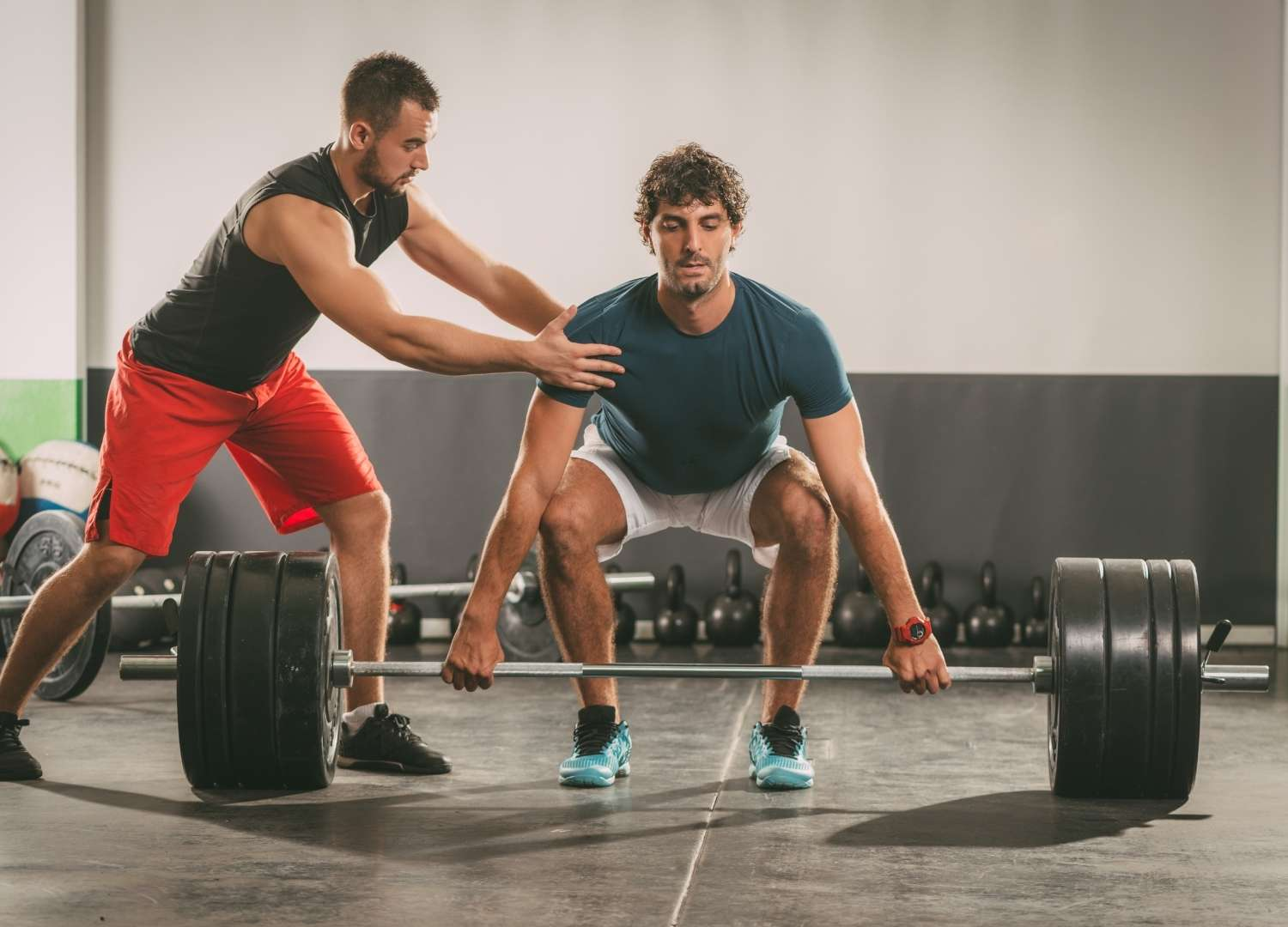 An instructor assisting a man in weight lifting