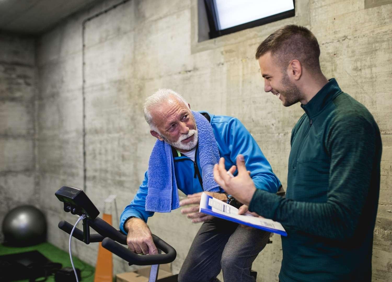 An instructor talking to an elder man