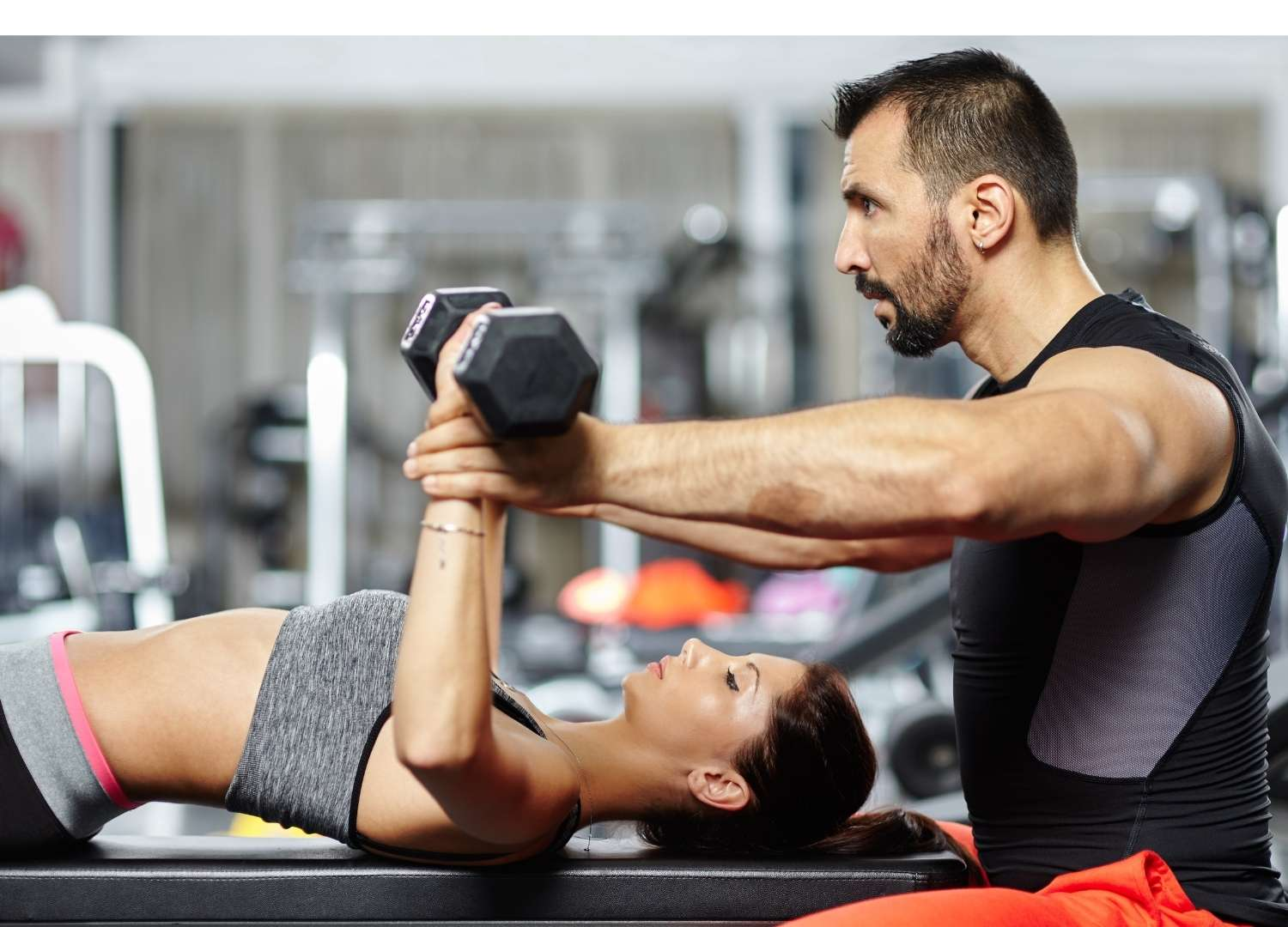 Instructor helping out a woman in weight lifting