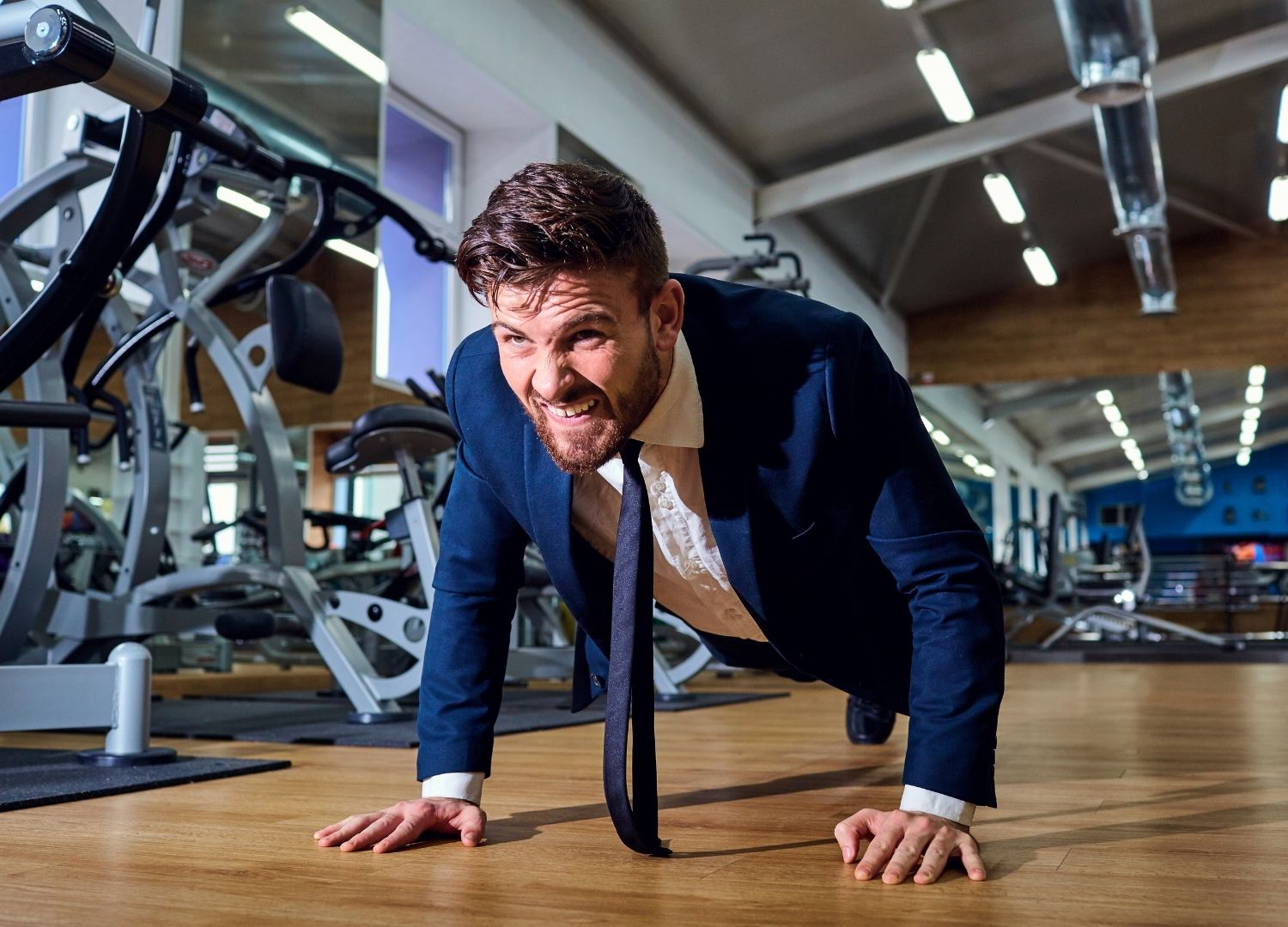 Man performing push-ups in a corpoarte suit