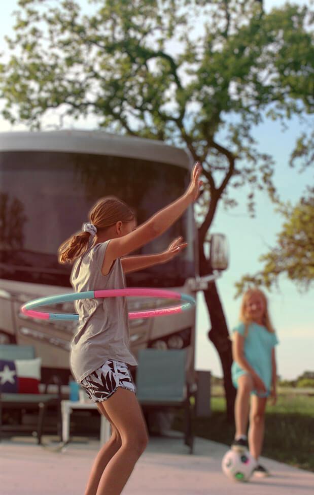 Family having fun hula hooping in large RV site
