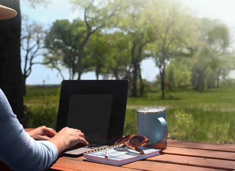 woman working on laptop enjoying nature at Austonia RV Resort