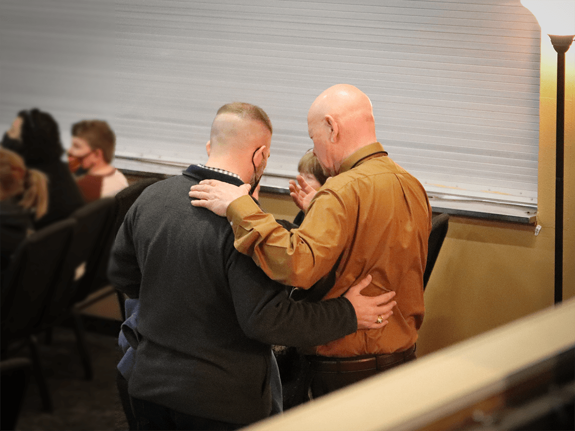 Deacon praying with someone from the congregation.
