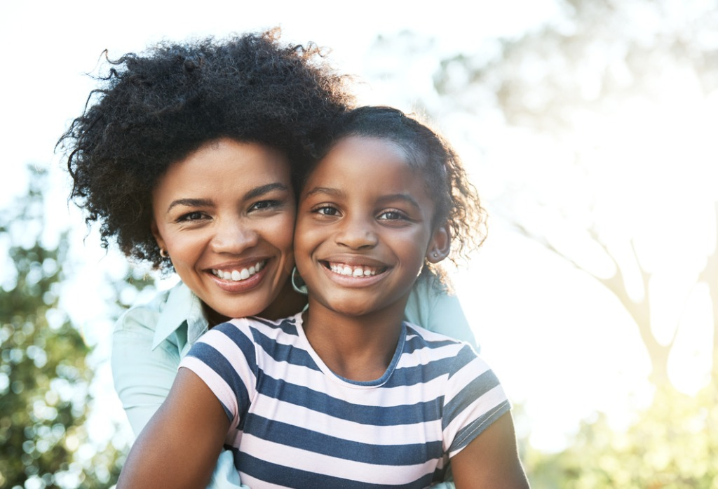 A mother and young daughter are outdoors, looking at the camera and smiling.