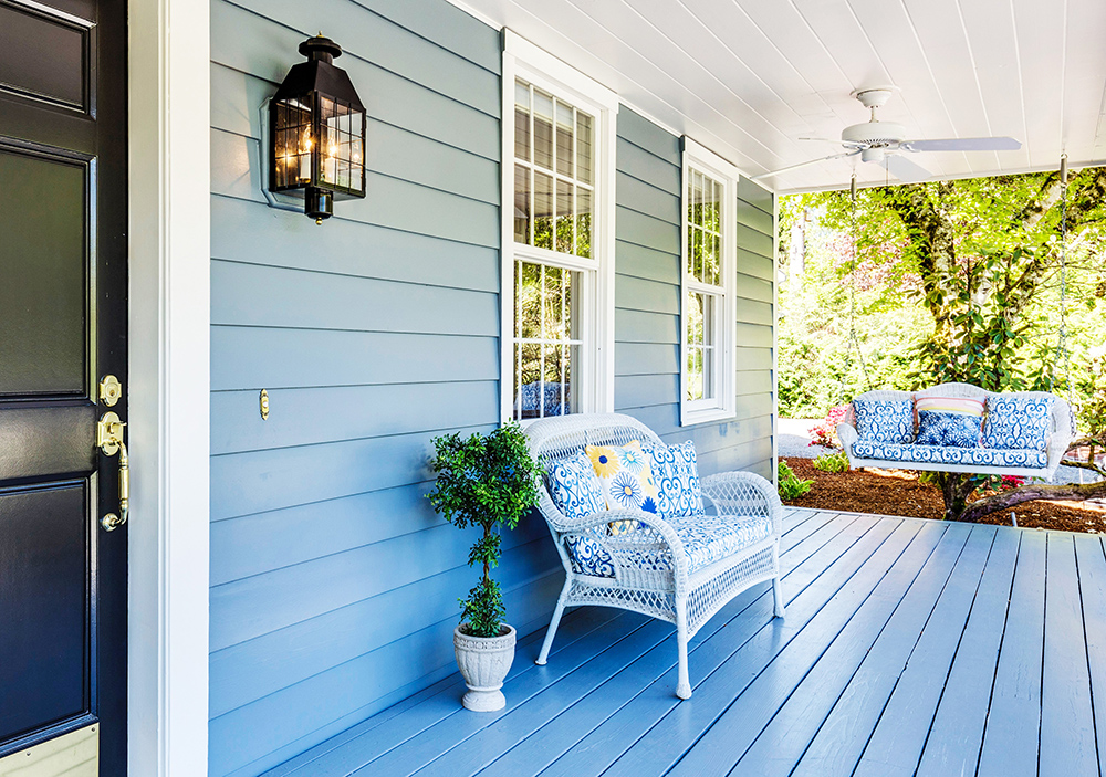 A pretty front porch in the spring. Featuring a white wicker loveseat and porch swing with blue accents.