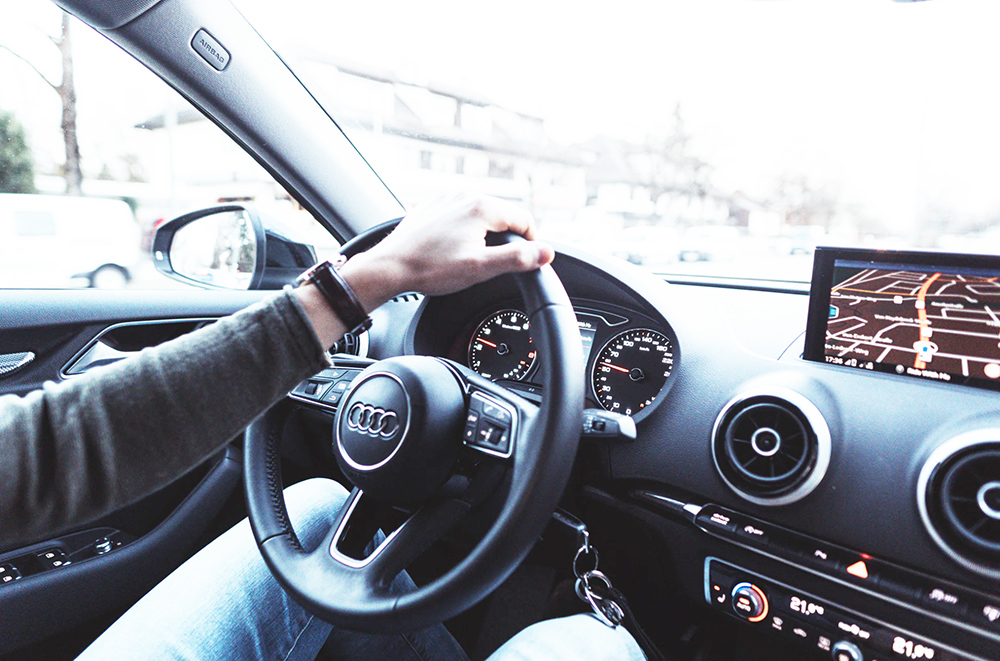 View from the passenger seat looking onto the driver's side. Just the driver's hand is seen casually steering the car in an Audi.