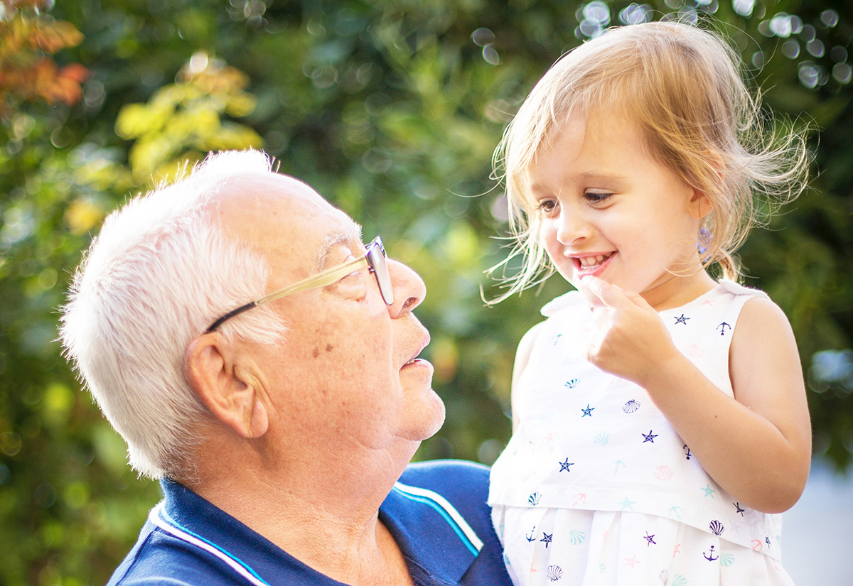 A grandfather holds his granddaughter and they smile at each other out in the yard.