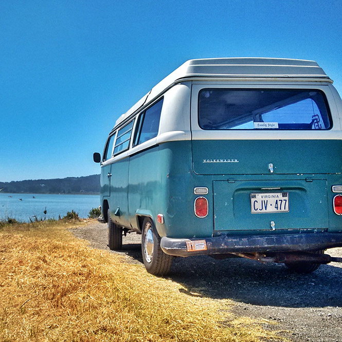 A blue vintage camper parked overlooking a lake.