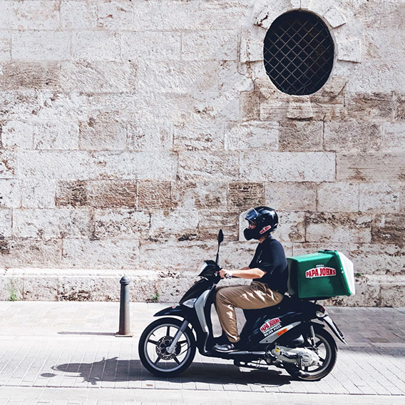 A side shot of a delivery driver on a moped with a Papa John's pizza box on the back.
