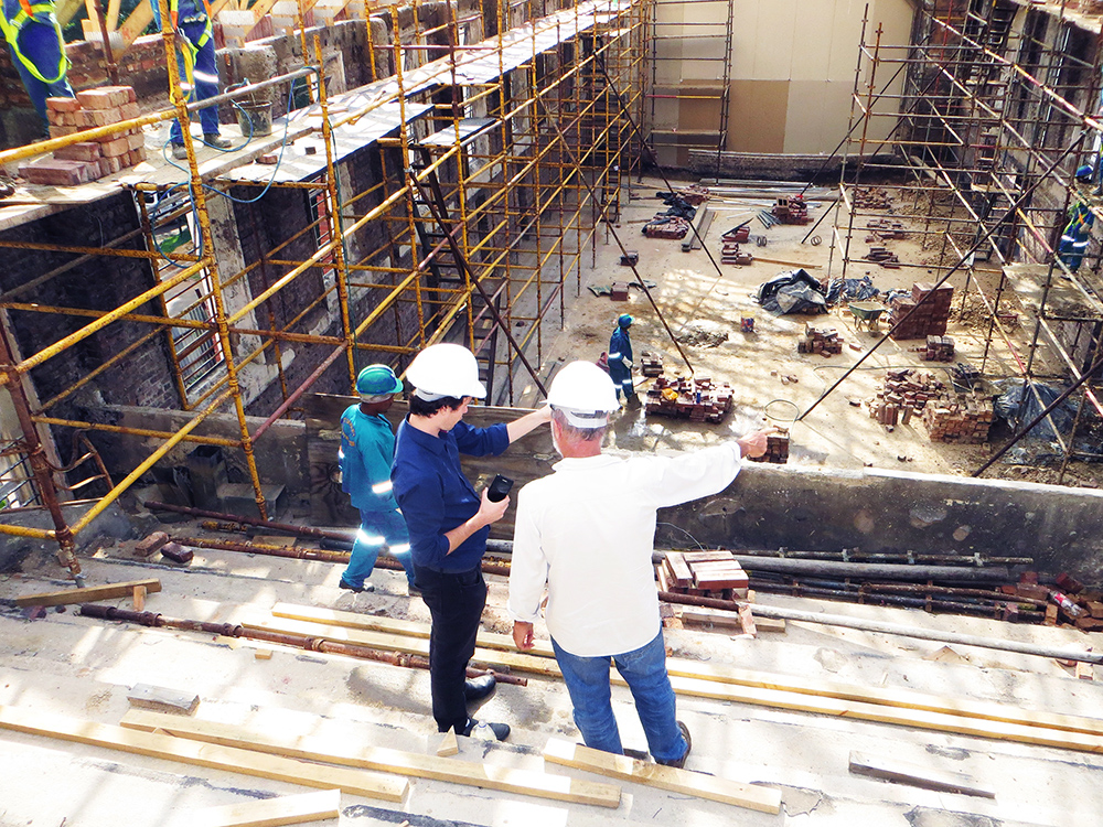 Two men in white hardhats overlook the construction zone of a large building. They are pointing to one side of the building, discussing something.