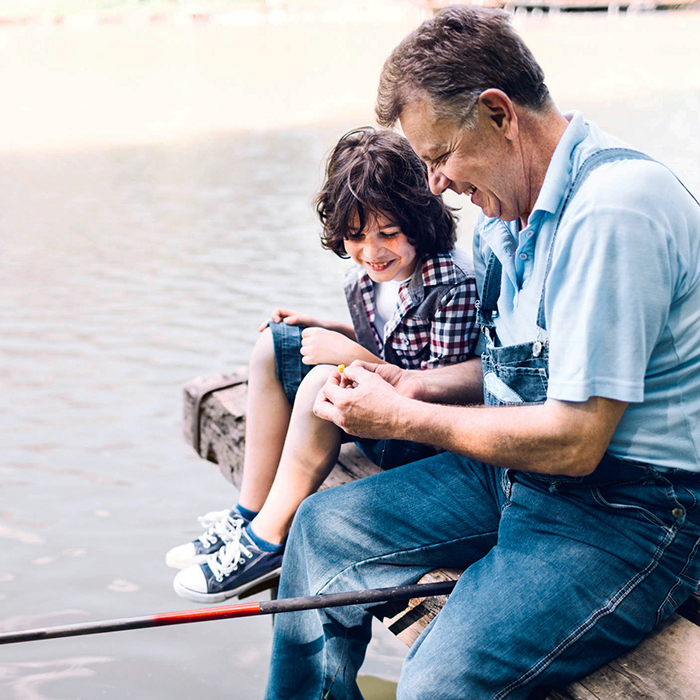 A grandfather and grandson are sitting on a dock fishing on a sunny day.