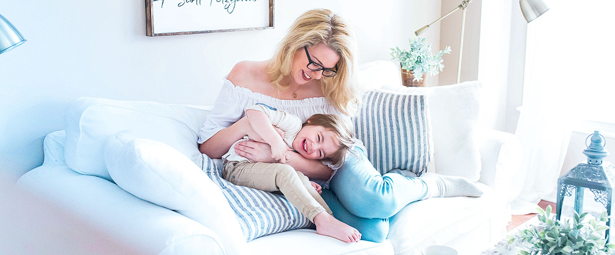 A mother and her son playfully cuddle on a white couch in a bright and modern living room. Mother is smiling at her son and he is laughing.