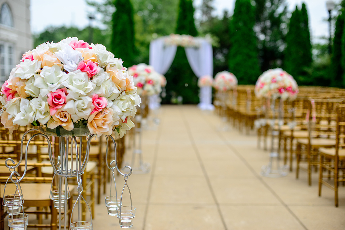 A picture of a wedding alter outdoors, with chairs and flower in the foreground.