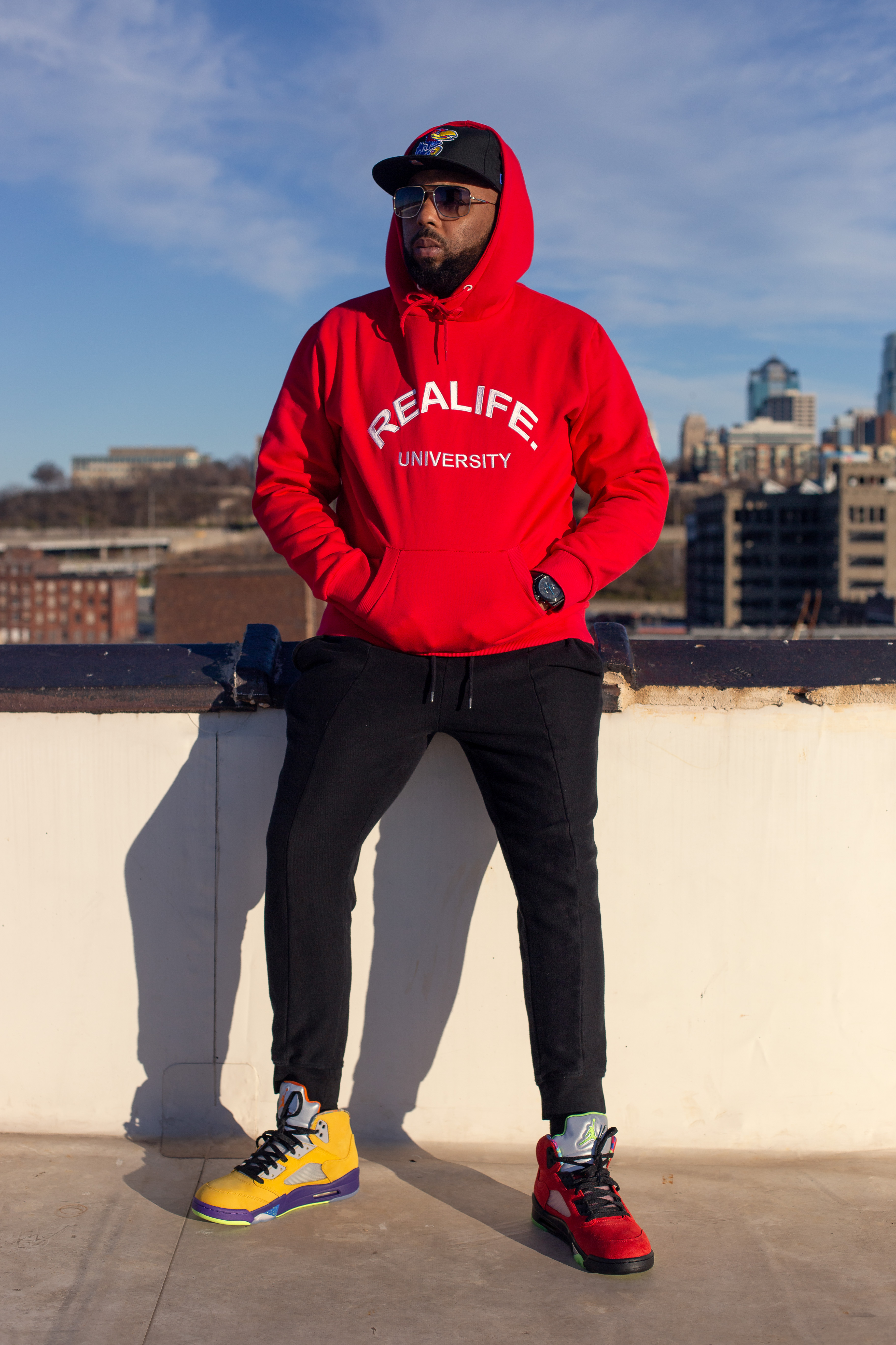 A man in a red hood sitting on top of a knee wall.