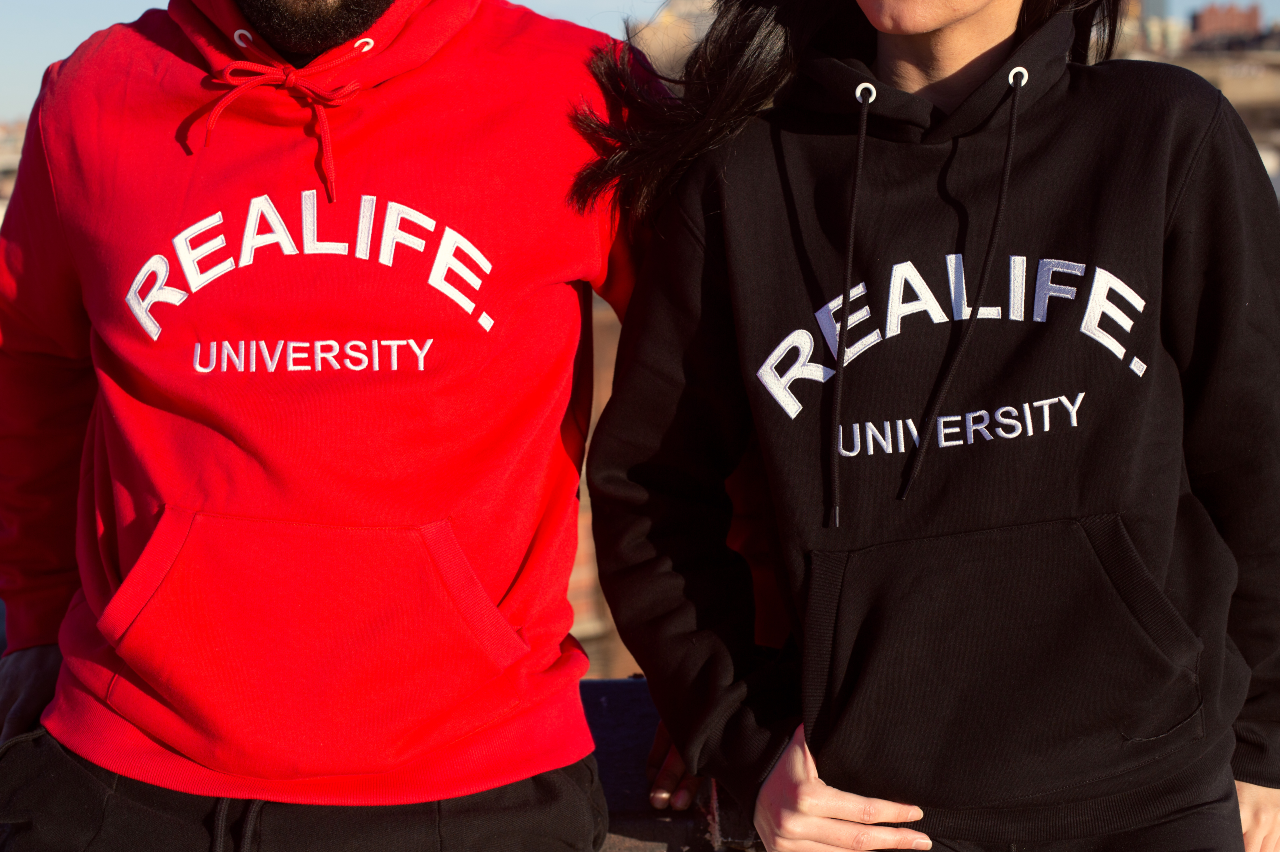 A man and women with hoodies on. Focused in on the red and black hoodies that they are wearing.