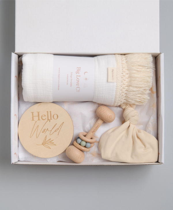 Newborn aby boy gift hamper with white fringed swaddle wrap, teething rattle, hello world sign and knot baby beanie