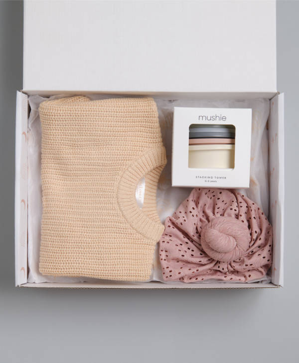 Newborn baby girl gift hamper with cream oversized knitted baby jumper, blush pink knot turban and mushie stacking cups