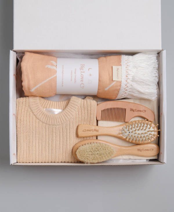 Newborn by girl gift hamper with cream oversized knitted baby jumper, peach fringe muslin swaddle wrap and wooden grooming set