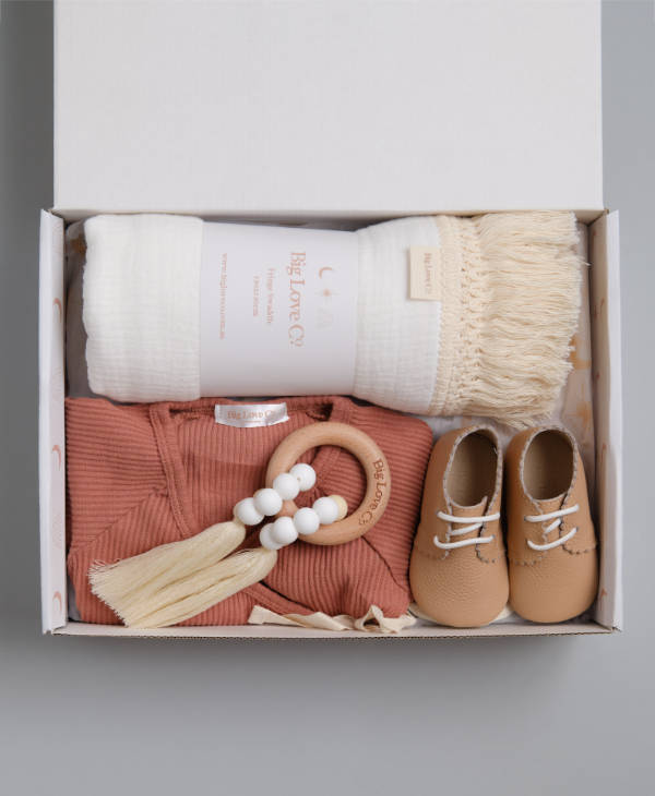 Newborn baby gift hamper for girl with white fringed swaddle wrap, ribbed baby romper, teething ring and leather baby shoes