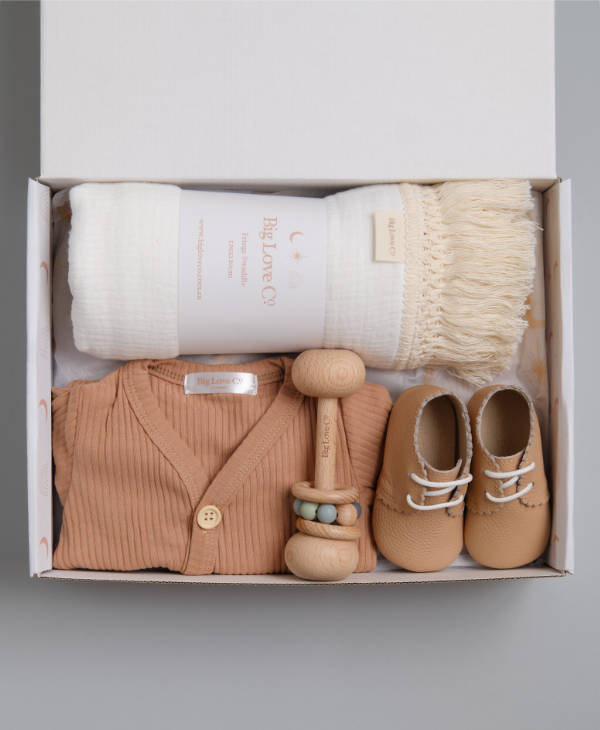 Baby gift hamper with white fringed newborn swaddle, ribbed baby romper, baby teething toy and leather baby shoes