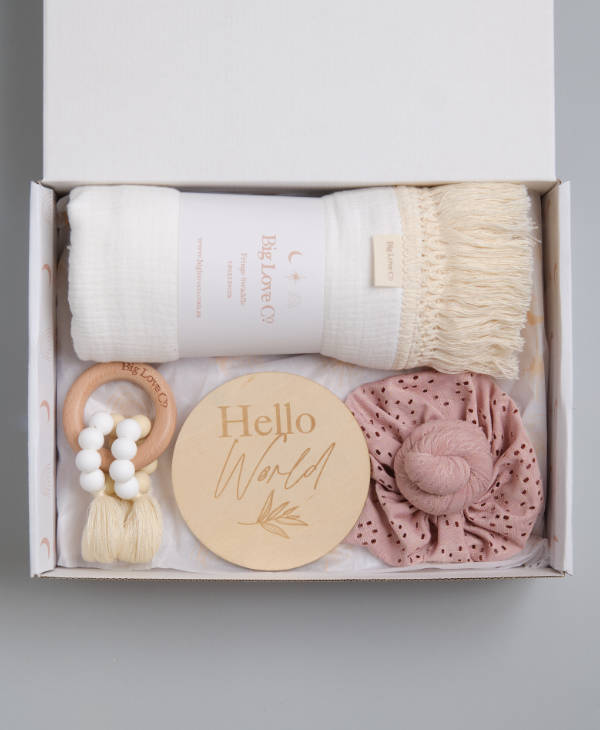 Newborn baby girl gift hamper with white fringed swaddle wrap, teething ring toy, hello world sign and knot baby turban