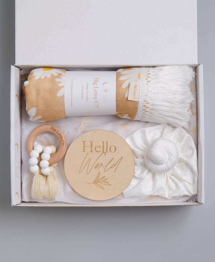 Newborn baby girl gift hamper with daisy fringed swaddle wrap, teething ring toy, hello world sign and knot baby turban