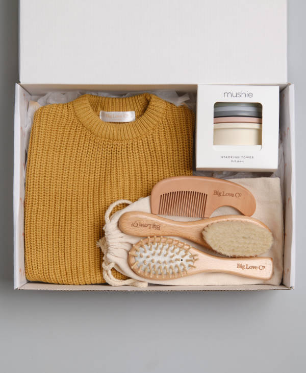 Newborn baby gift box with oversized knitted baby jumper, mushie stacking toys and wooden baby grooming set