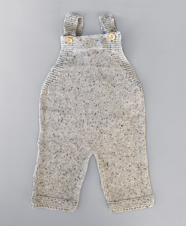 Speckled white knit overalls by Charlie and Bear are staple piece that can be worn all year round