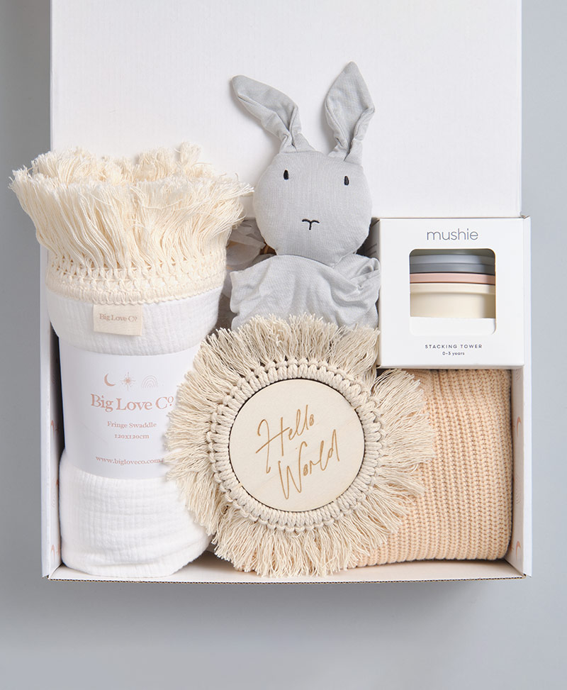 baby Boy gift box with white fringe swaddle, macrame hello world plaque, bunny comforter and mushie stacking cups.