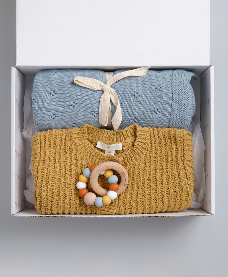 Sunset baby boy gift box with mustard knit cardigan, blue heirloom baby blanket and teething ring.