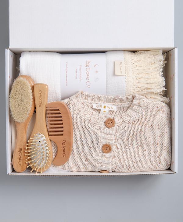 Gender neutral gift box with baby brush set, knit cardigan and white fringe swaddle.