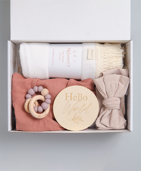 Hello baby gift box with blush baby romper, teething ring, topknot bow, hello world sign and white swaddle.