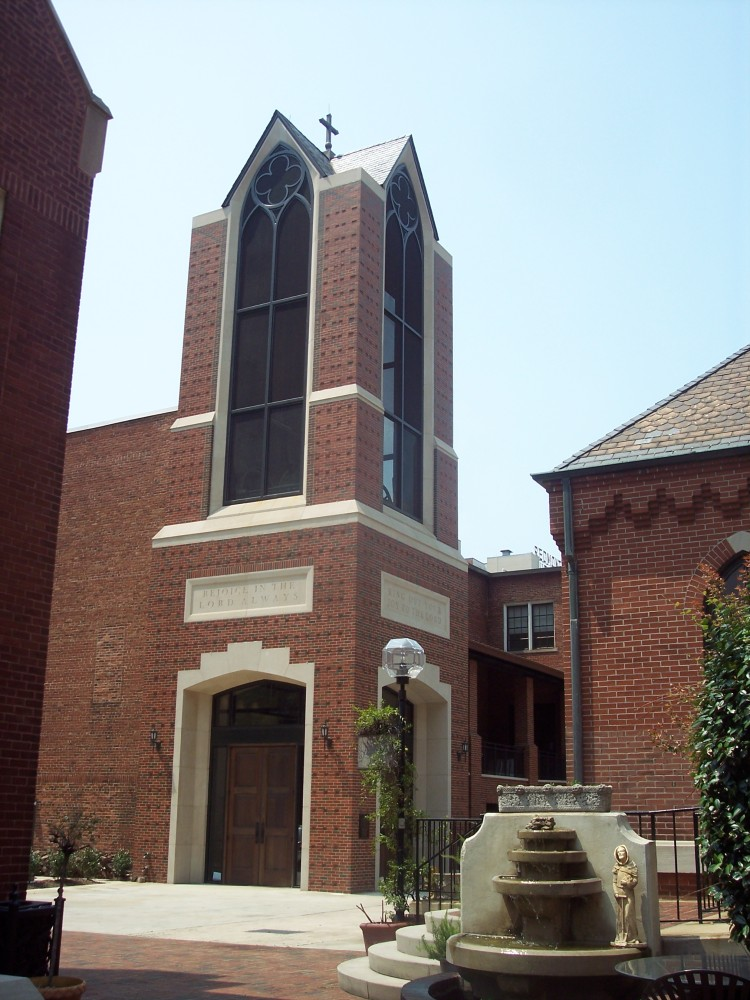 Modern square, brick tower with tall, vertical glass features on each face attached to a brick building and overlooking a courtyard.