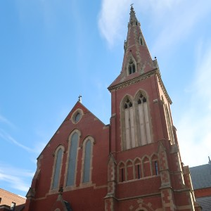Large urban brick gothic revival church with an attached tower on one side and a tall brick and stone spire with windows