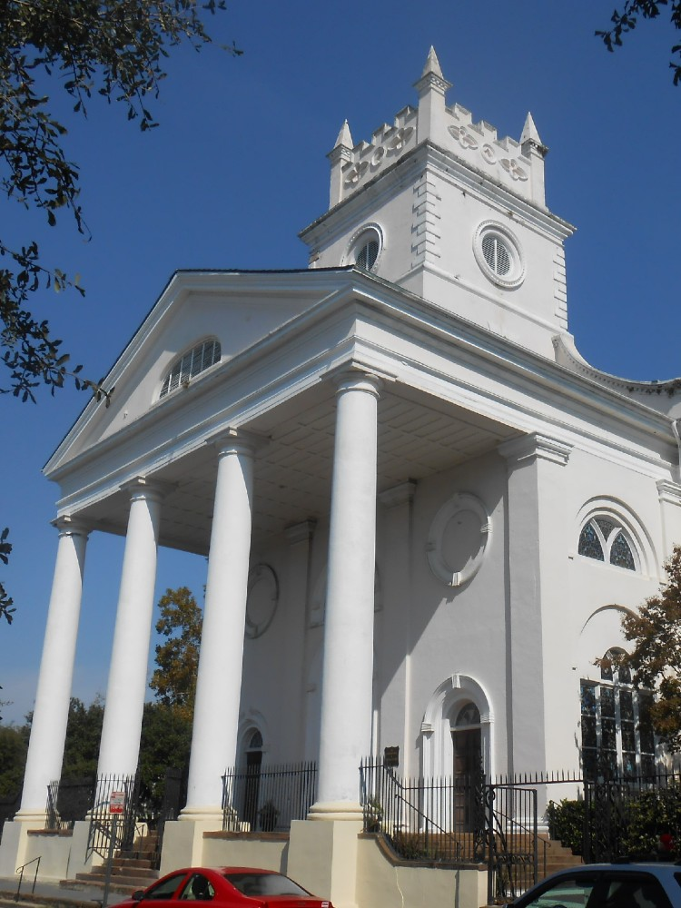 White historic colonial church in the style of Christopher Wren with white columns and a short square tower