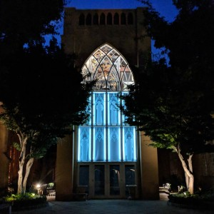 Contemporary tower on a courtyard photographed at night, with large, blue-backlight windows in the middle floor and clear windows onto the bells above.