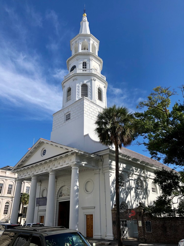 White colonial church in the style of Christopher Wren with white columns, and a large, imposing white steeple with multiple hexagonal layers and lantern