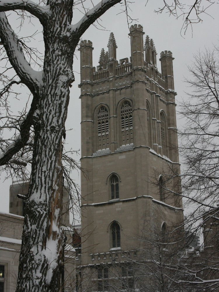 Gothic revival tower attached to a campus building covered in snow on a cold, overcast winter day
