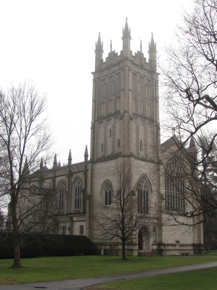 Gothic revival chapel with a large, tall square tower containing lancet windows and four small spires, one on each corner