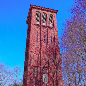 Freestanding square brick tower on a winters day against a bright blue sky