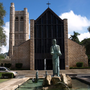 Copper statue in a fountain backed by modern stone church with large stained glass window, with square stone tower behind with rounded corners