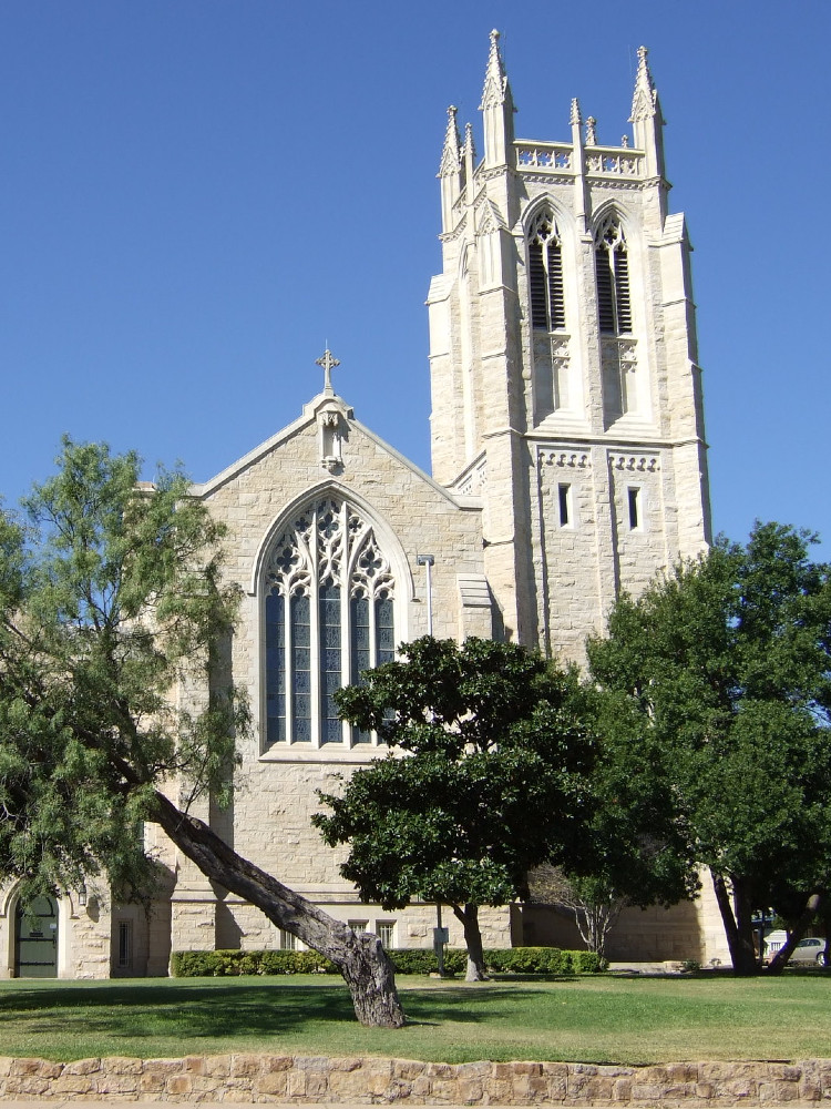 White stone gothic revival church with a large square tower on one side.