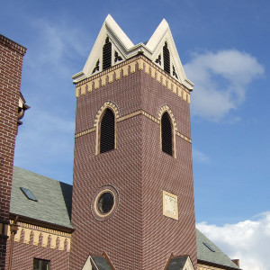 Contemporary brick tower with a four-point roof, a round window, and a clock, attached to a brick building.