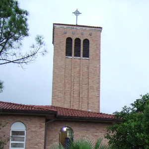 A tall, square brick tower of simple design, with three Romanesque windows at the top opening into the belfry and a tile roof