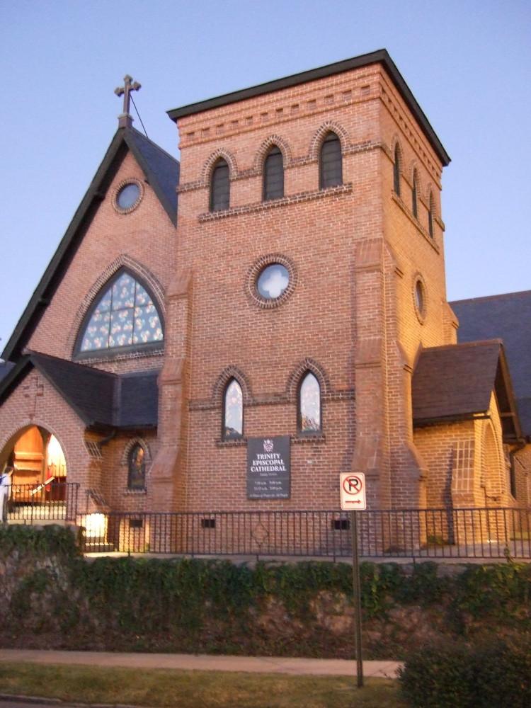 Broad, short square brick tower at corner of a brick urban church